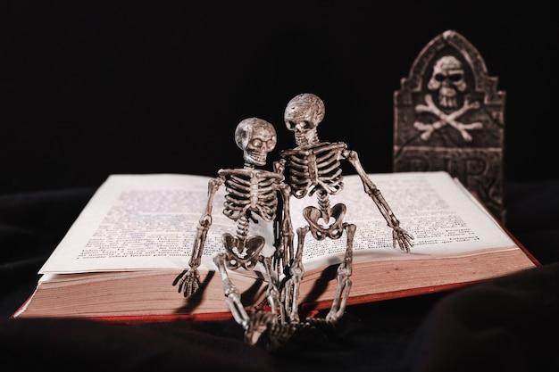 Halloween-concept met skelet op boek en grafsteen