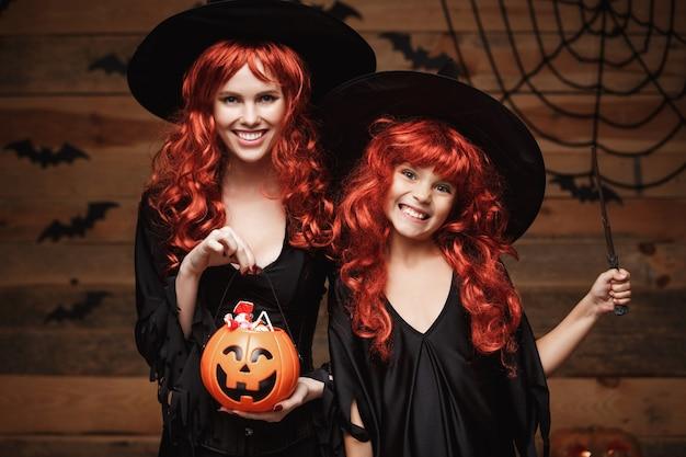 Halloween concept mooie blanke moeder en haar dochter met lang rood haar in heksenkostuums...
