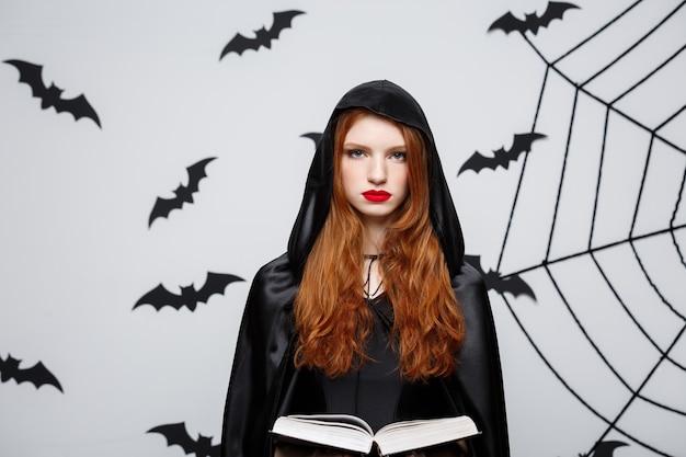 Halloween-concept - mooie donkere priester die spreuk met magisch boek op grijze muur giet.