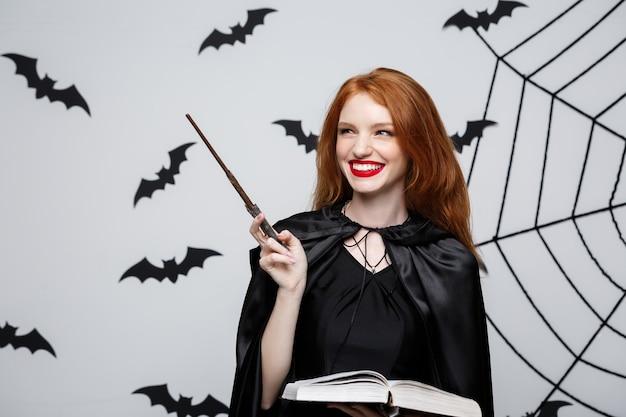Halloween-concept - mooie heks die met magische stok en magisch boek op grijze muur speelt.