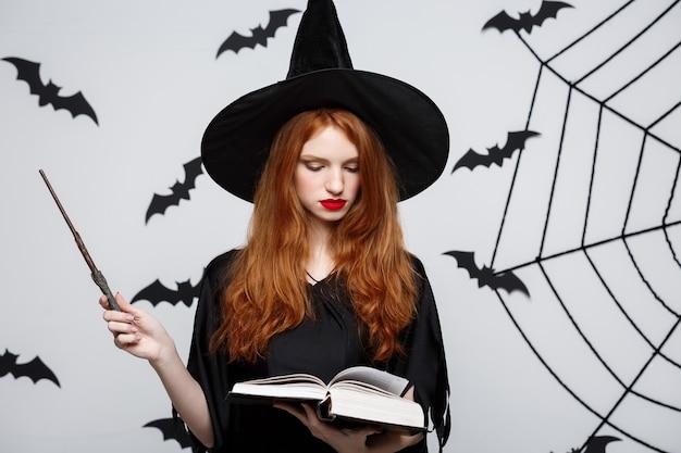 Halloween-concept - mooie heks die met magische stok op grijze muur speelt.