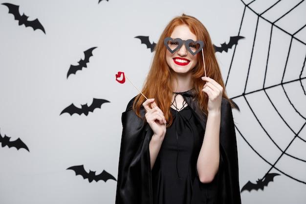 Halloween-concept - mooie meisjes in zwarte heksenjurken met feestrekwisieten.