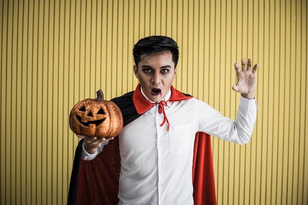 Halloween concept van jonge aziatische man in kostuum dracula en houd halloween oranje pompoen op gele achtergrond. portret van tiener man verkleed als dracula voor het vieren van halloween festival.