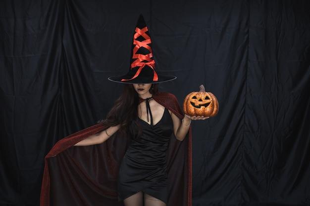 Halloween concept van jonge aziatische vrouw in kostuum heks en houd halloween oranje pompoen op zwarte doek achtergrond. portret van tiener vrouw verkleed als heks voor het vieren van halloween festival.