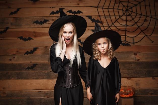 Halloween-concept vrolijke moeder en haar dochter in heksenkostuums schokkend met iets