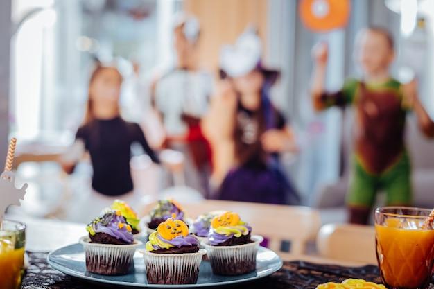 Halloween cupcakes. close-up van blauw bord met mooie heldere halloween cupcakes staande op de tafel in de buurt van glas jus d'orange