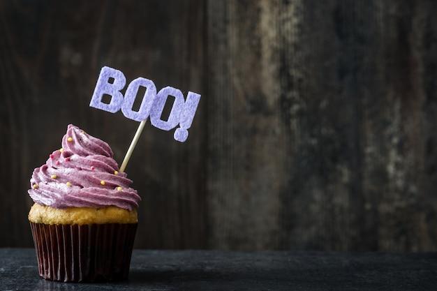 Halloween cupcakes en spinneweb op rustieke houten achtergrond