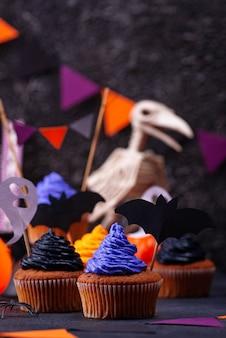 Halloween cupcakes met zwarte, paarse en oranje crème en decor