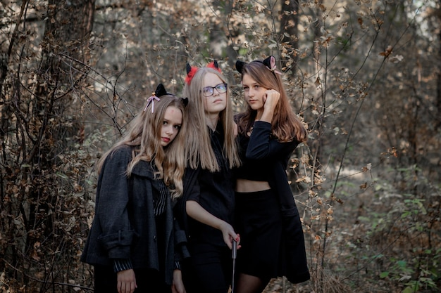 Halloween-daemon, maniak en heks in het bos. tieners in halloween-kostuums in het bos.