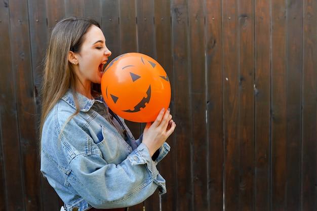 Halloween-de herfstachtergrond met meisje die oranje luchtimpuls houden