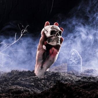 Halloween-de holdingsschedel van de zombiehand bij begraafplaats Gratis Foto