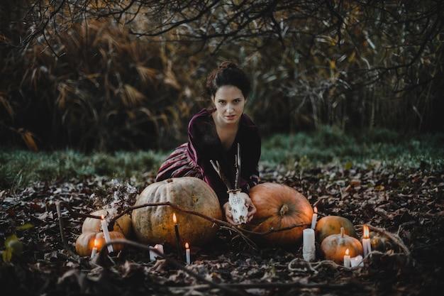 Halloween decor. vrouw ziet eruit als een heks zit