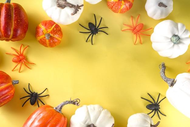 Halloween decoratie achtergrond met pompoenen, spinnen op witte tafel achtergrond bovenaanzicht kopie ruimte