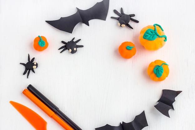 Halloween decoratie. frame van pompoenen en spinnen met de hand gemaakt van plasticin