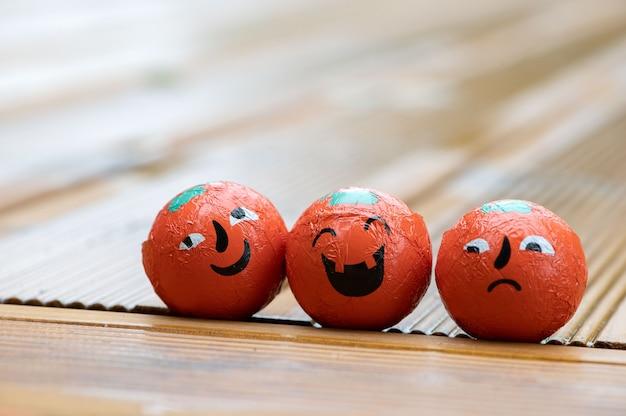 Halloween-decoratieachtergrond met drie pompoenensnoepjes met emotiegezichten op het huis houten terras