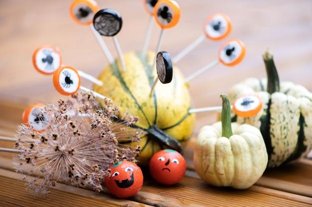 Halloween-decoratieachtergrond met pompoenen en snoepgoed op het houten terras van het huis