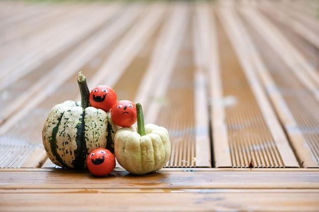 Halloween-decoratieachtergrond met pompoenen en snoepsnoepjes met emotiegezichten op het houten terras