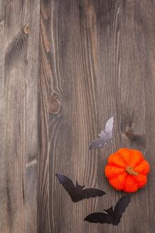 Halloween-decoratieconcept - zwarte knuppels en oranje pompoen op donkere houten achtergrond