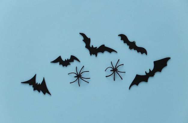 Halloween, decoraties en eng concept. spinnen en zwarte vleermuizen vliegen over blauw