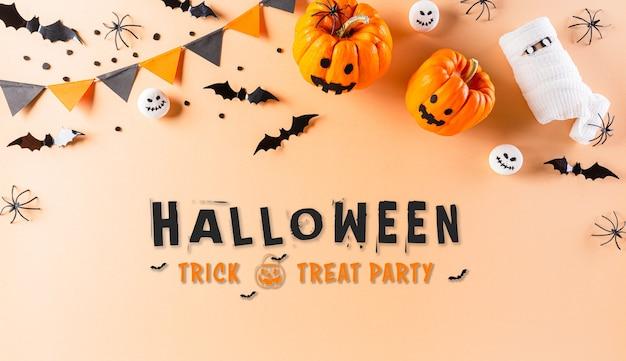 Halloween-decoraties gemaakt van pompoen, papieren vleermuizen en zwarte spin op pastel oranje achtergrond. plat lag, top uitzicht met halloween-tekst