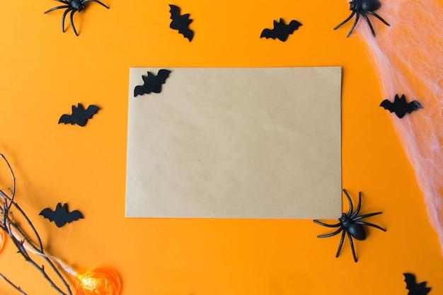 Halloween-decoraties, pompoenen, vleermuizen, web, insecten op oranje achtergrond. halloween-feest wenskaart met kopie ruimte. plat lag, bovenaanzicht.