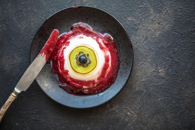 Halloween-dessert bloody eye van vanille panna cotta en kiwi met bessensiroop Premium Foto