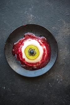 Halloween-dessert bloody eye van vanille panna cotta en kiwi met bessensiroop
