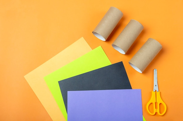 Halloween diy en creativiteit voor kinderen. voorbereidingshulpmiddelen: toiletrolbuis, schaar, veelkleurig papier voor het maken van decoratiemonster. kinderen knutselen milieuvriendelijk hergebruik recyclen
