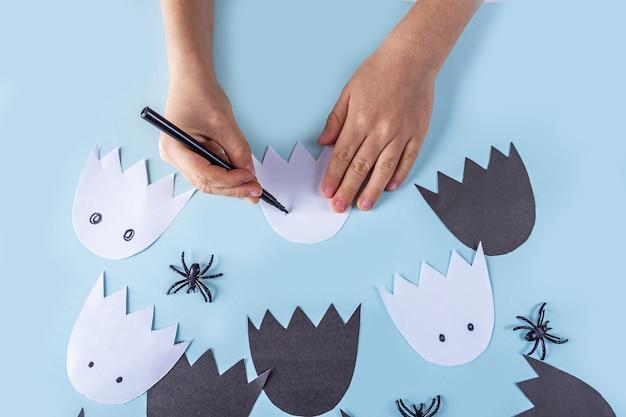 Halloween diy en kinderen creativiteit. stapsgewijze instructies om een krans van geesten van papier te maken