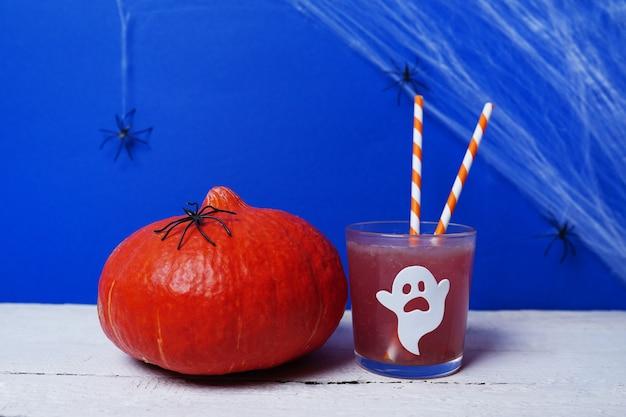 Halloween-drankjes met pompoen voor een kinderfeestje op wit hout en blauwe scène met spinnen