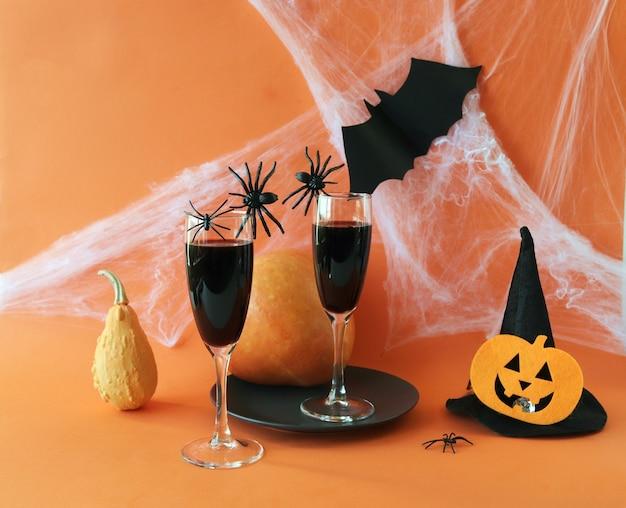 Halloween drinkt wijnpompoenspinnen en mystieke decoratie op een feloranje achtergrond