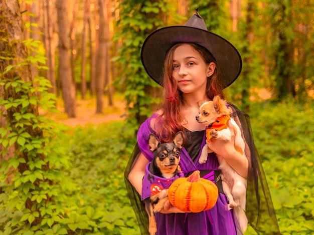 Halloween en feest. meisje in heksenkostuum met halloween-pompoen houdt buiten een hond vast.