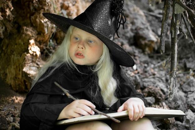 Halloween en heksen. kind in de afbeelding van een heks met wit haar in een donkere grot, vakantie
