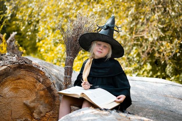 Halloween en heksen. kind in een heksenkostuum. het kind zit op een boom met een boek en een toverstaf. herfst, bos