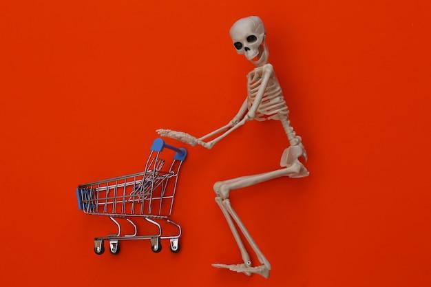 Halloween, eng thema. skelet en winkelwagentje op oranje.
