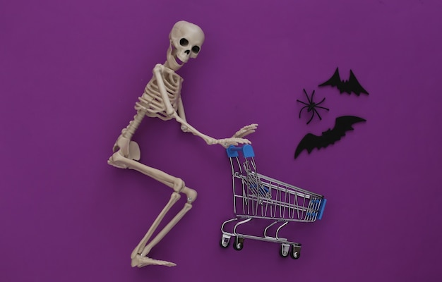 Halloween, eng thema. skelet en winkelwagentje op paars met spinnen en vliegende decoratieve vleermuizen.