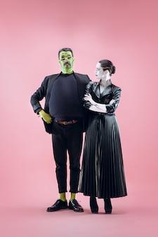 Halloween-familie. gelukkig paar in halloween-kostuum en make-up. bloedig thema: de gekke maniakgezichten op roze studioachtergrond