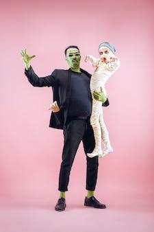 Halloween-familie. gelukkig vader en kinderen meisje in halloween kostuum en make-up. bloedig thema: de gekke maniakgezichten op roze studioachtergrond