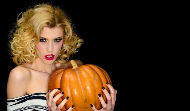 Halloween feest. sensueel meisje met grote pompoen. sexy heksenvrouw met jack-o-lantern. ruimte kopiëren.