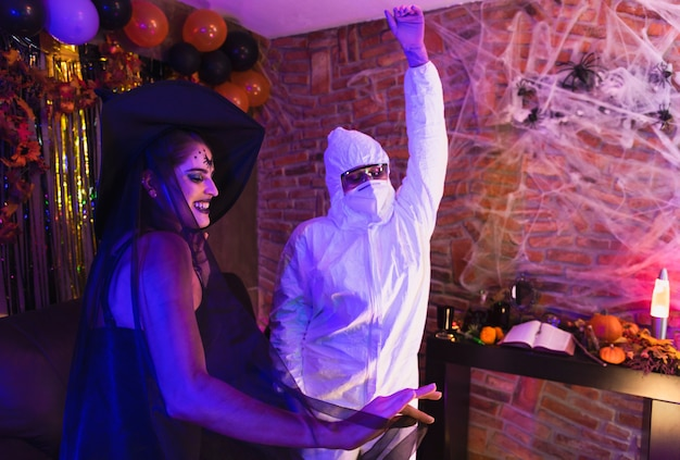 Halloween-feest thuis, groep vrienden in kostuums met plezier dansen