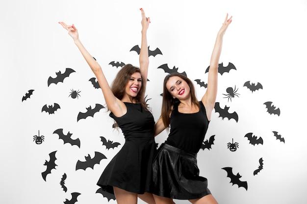 Halloween feest. twee brunette meisjes met zwarte jurken hebben plezier op de achtergrond van de muur met vleermuizen en spinnen.