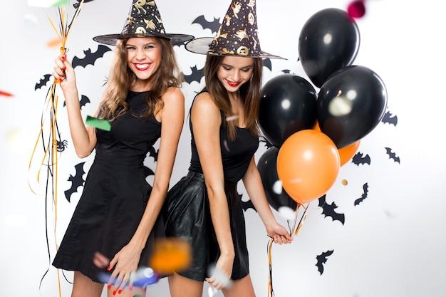 Halloween feest. twee prachtige meisjes in zwarte jurken en heksenhoeden hebben plezier met ballonnen en confetti. .