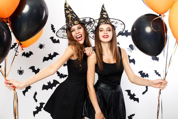 Halloween feest. twee prachtige vrouwen in zwarte jurken en heksenhoeden houden zwarte en oranje ballonnen op de achtergrond van de muur met vleermuizen. .
