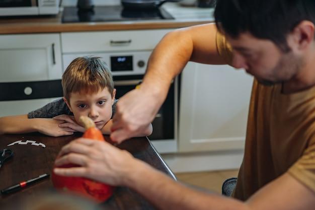Halloween-feest voorbereiden. blanke man met zijn schattige 6-jarige zoon die ogen op een pompoen trekt om traditionele jack-lantaarn te maken. afbeelding met selectieve aandacht. hoge kwaliteit foto