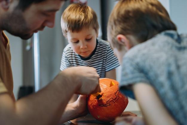 Halloween-feest voorbereiden. blanke man met zijn schattige zonen die ogen uitsnijden op een pompoen om traditionele jack-lantaarn te maken. afbeelding met selectieve aandacht.