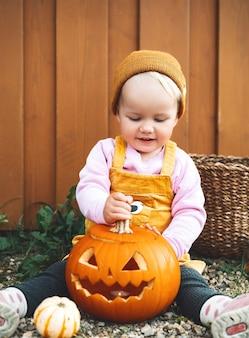 Halloween-feestje voor kinderen schattig klein kind met pompoenen op houten achtergrond