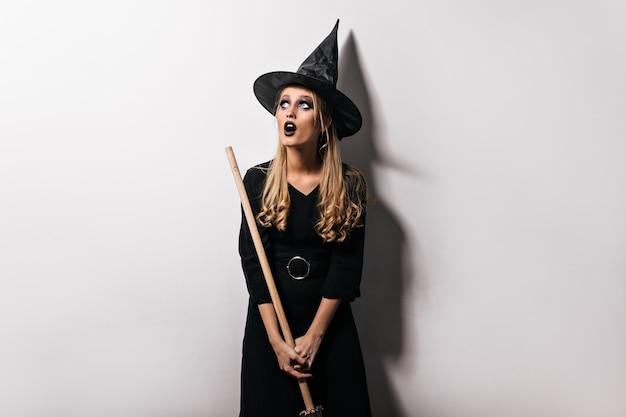 Halloween-foto van vrij blondemeisje met magische bezem. binnen schot van nieuwsgierige jonge heks in zwarte hoed.