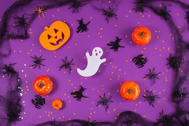 Halloween-frame met pompoenenspook en spinnen op paarse achtergrond