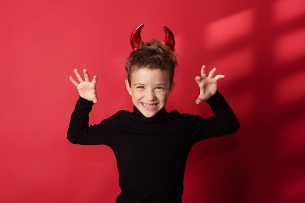 Halloween gelukkig kind lacht hardop met duivelse hoorns tegen een rode studioachtergrond