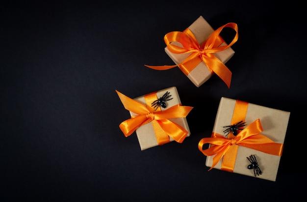 Halloween geschenkdozen met decoratieve spinnen bovenaanzicht op donkere achtergrond. ruimte voor uw tekst